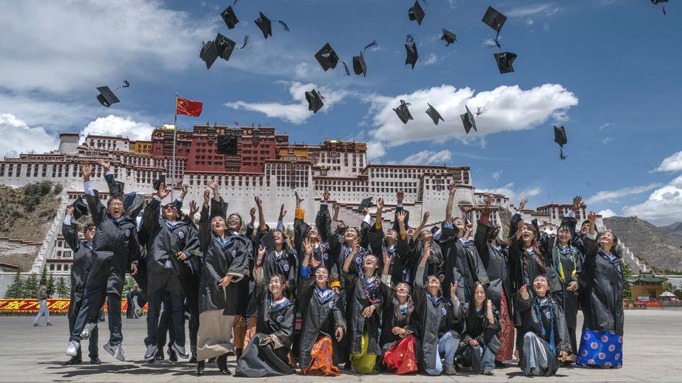 Heile Welt mit hochfliegenden Hüten der Studierenden in Lhasa mit demPotala-Palast im Hintergrund.