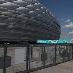 """Vor der Allianz-Arena in München hängen über einem Eingangsbereich türkis-grüne Banner mit """"Uefa Euro 2020""""-Logo"""