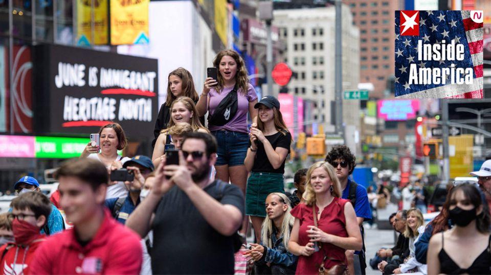 Passanten in New York City (USA) beobachten auf dem Times Square ein Pop-up-Event