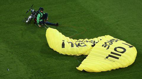 Ein Greenpeace-Aktivist sitzt mit einem gelben Fallschirm auf dem Fußballrasen in München