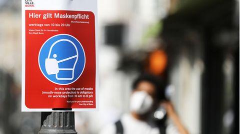 Ein Schild weist auf die Maskenpflicht hin, im Hintergrund sieht man verschwommen eine Person mit Mund-Nasen-Schutz