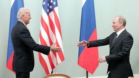 Joe Biden und Wladimir Putin reichen sich die Hände vor den Flaggen von Russland und den USA
