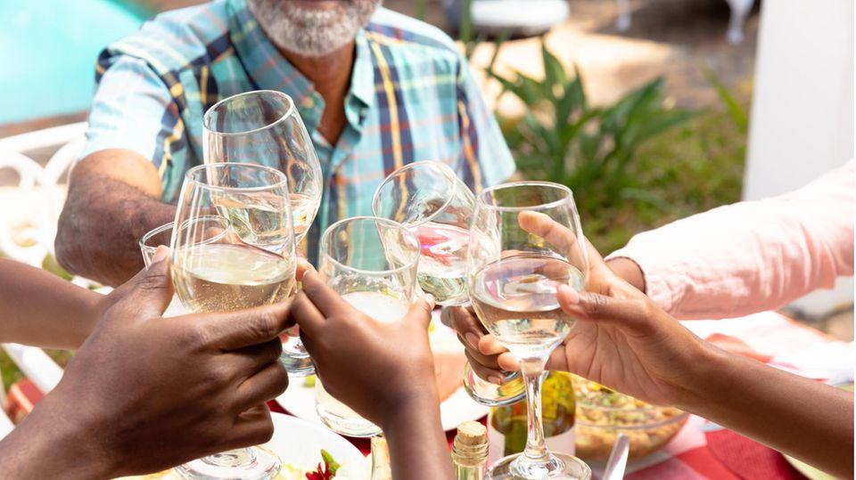 Mehrere Hände halten Wein- oder Wassergläser und stoßen über einem gedeckten Tisch an