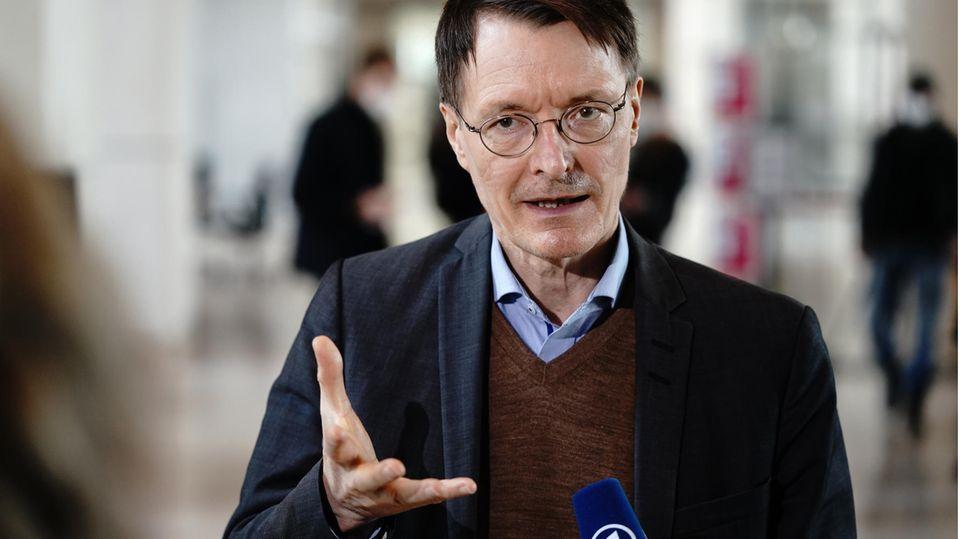 Karl Lauterbach spricht in ein Mikrofon und gestikuliert