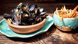 Moules frites  Zutaten:5 große mehligkochende oder vorwiegend festkochende Kartoffeln, 2 kg küchenfertige frische Miesmuscheln, 4–6 Schalotten, 2 Knoblauchzehen, Olivenöl zum Anschwitzen, 400 ml trockener Weißwein, 1 TL Kräuter der Provence, 1 l Pflanzenöl, Salz  Zubereitung: Die Kartoffeln schälen, in dicke Stifte schneiden und beiseitestellen. Die Muscheln waschen, bereits geöffnete und angebrochene wegwerfen. Die Schalotten und den Knoblauch abziehen, fein hacken und in reichlich Olivenöl in einem Topf glasig anschwitzen. Mit dem Weißwein ablöschen und den Sud auf die Hälfte reduzieren. Dann die Muscheln und die Kräuter der Provence in den Topf geben. Alles gut umrühren und bei geschlossenem Deckel 10–15 Minuten kochen lassen. Ab und zu umrühren. Die im Anschluss an die Garzeit geschlossenen Muscheln aussortieren und wegwerfen. (Ungeöffnete Muscheln sind nicht zum Verzehr geeignet.) Die Kartoffelstifte in reichlich heißem Öl in einem Topf goldbraun frittieren. Dann mit einer Schöpfkelle aus dem Öl nehmen und auf Küchenpapier abtropfen lassen. Mit etwas Salz würzen. Die Muscheln mit dem Sud auf tiefen Tellern anrichten und mit den Pommes frites zusammen servieren