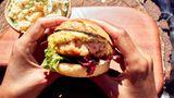 Shrimp-Burger mit Ananas Cole Slaw  Zutaten:  Für den Coleslaw: ½ Kopf Weißkohl, 1 kleine Ananas, 2 Becher Crème fraîche (à ca. 150 g), 1 TL Currypulver, frisch gemahlener schwarzer Pfeffer, 1 unbehandelte Limette  Für die Burgersauce:1 Bund frischer Dill, 1 EL Dijonsenf, 4 EL Mayonnaise  Für die Shrimp-Pattys: 500 g rohe, küchenfertige Riesengarnelen in der Schale (Black Tiger Prawns), ½ Limette, Salz, frisch gemahlener schwarzer Pfeffer, 2 EL Maisstärke, Butter zum Anbraten  Ausserdem: 2 Briochebrötchen bunter Blattsalat  Zubereitung:Für den Coleslaw den Strunk des Weißkohls entfernen, den Kohl in feine Streifen schneiden, waschen und trockenschütteln. Die Ananas schälen, das harte Strunkstück entfernen und das Fruchtfleisch in kleine Würfel schneiden. Den Weißkohl und die Ananas mit der Crème fraîche vermengen. Mit dem Currypulver und Pfeffer würzen. Die Limette heiß abwaschen und die Schale fein abreiben. Diese für die Burgersauce aufheben. Die Limette pressen und den Saft unter den Coleslaw rühren. Den Coleslaw abgedeckt für mindestens 2 Stunden an einem kühlen Ort durchziehen lassen. Für die Burgersauce den Dill waschen, trockenschütteln und fein hacken. Den Dill mit dem Senf, der Mayonnaise und der abgeriebenen Limettenschale glatt verrühren. Für die Shrimp-Pattys die Garnelen aus der Schale lösen und in eine Schüssel geben. Anschließend mit dem Saft der ½ Limette sowie je 1 Prise Salz und Pfeffer würzen. Die gewürzten Garnelen mit einem Stabmixer grob pürieren. Die Maisstärke dazugeben und alles zu einer homogenen Masse verkneten. Aus der Masse 2 Pattys formen und in etwas Butter in einer Pfanne von beiden Seiten kross anbraten. In der Zwischenzeit die Briochebrötchen halbieren, auf den Innenseiten anrösten und auf Teller verteilen. Den Blattsalat waschen und trockenschütteln. Die unteren Brötchenhälften mit Salat belegen, Burgersauce daraufgeben und die Shrimp-Pattys obenauf legen. Die oberen Brötchenhälften aufsetzen. Die Burger mit dem Coleslaw und je ein