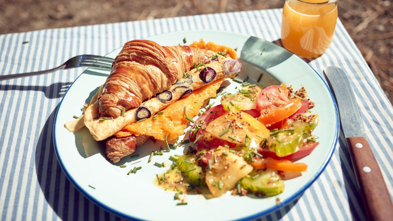 Croissant-Sandwich  Zutaten:Croissants (frisch oder vom Vortag), 150 g geriebener Cheddar, 2 reife Tomaten, 4 Frühlingszwiebeln, Olivenöl zum Anschwitzen, 2 Eier (Größe L), Salz, frisch gemahlener schwarzer Pfeffer  Zubereitung: Die Croissants aufschneiden und auf den Schnittflächen in einer beschichteten Pfanne ohne Fettzugabe anrösten. Danach auf Tellern beiseitelegen. Den Cheddar in die Pfanne geben, schmelzen lassen und kross anbraten. Den knusprig gebratenen Käse halbieren und auf den unteren Croissanthälften verteilen. Die Tomaten waschen, den Stielansatz herausschneiden und die Tomaten in Scheiben schneiden. Die Frühlingszwiebeln putzen, waschen und in Ringe schneiden. Etwas Olivenöl in der Pfanne erhitzen und die Frühlingszwiebeln darin anschwitzen. Dann die Eier aufschlagen, zufügen und alles zu einem Omelett braten. Mit Salz und Pfeffer würzen. Zum Anrichten das Omelett auf den Käse geben, die Tomatenscheiben darauf verteilen und die obere Hälfte der Croissants aufsetzen. Dazu passt Tomatensalat mit Schnittlauch, starker Kaffee und Orangensaft.