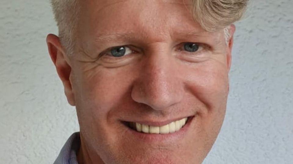 Ein weißer Mann mit schwungvollem, grau-blonden Seitenscheitel zeigt beim Lächeln seine Zähne