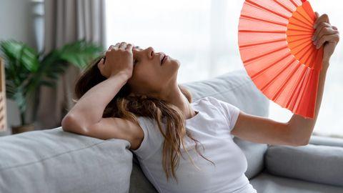Erschöpft Frau liegt mit Fächer auf der Couch