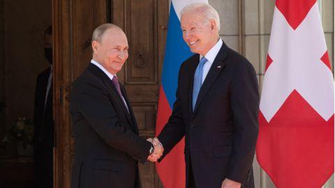 Biden und Putin geben sich die Hand und lächeln