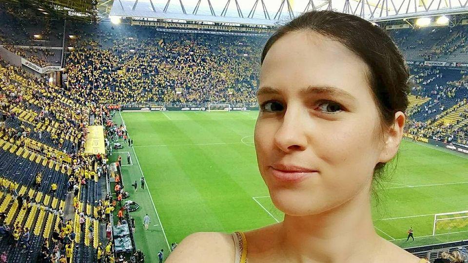 Unsere Autorin macht ein Selfie vor einem Fußballfeld