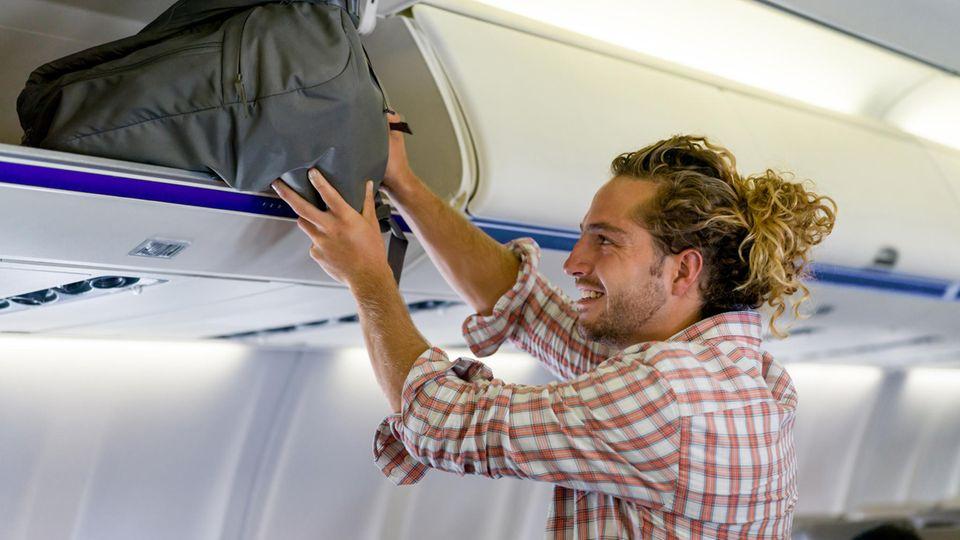 Ein Mann verstaut sein Handgepäck im Flugzeug