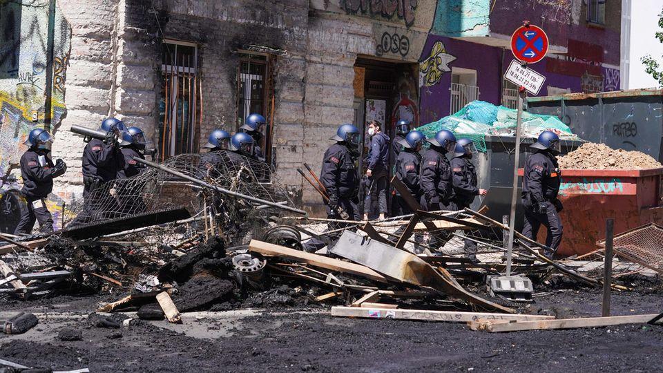 Polizisten gehen in der Rigaer Straße in Berlin-Friedrichshain mit einemRammbock neben einer Barrikade entlang