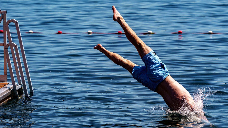 Ein junger Mann springt von einer Schwimmplattform aus in einen zum Schwimmen abgesperrten Bereich der Kieler Förde