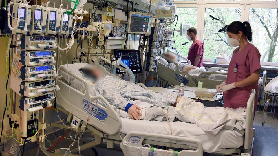 In einem Krankenhaus in Halle (Saale) arbeiten Pfleger auf der Intensivstation mit Covid-19 Bereich am Bett eines Patienten von Patienten.
