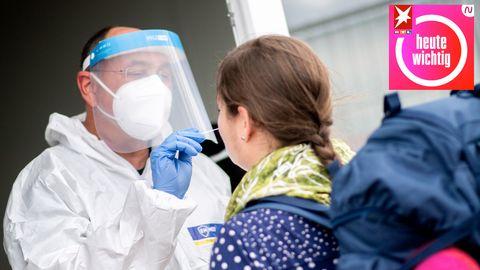 Ein Mitarbeiter eines Testcenters in Niedersachsen nimmt einen Abstrich von einer jungen Frau