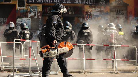 Ein Polizist in voller Kampfmontur trägt eine Motorsäge hinter einer Polizeikette vorbei
