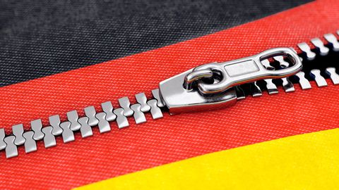 Ein Reißverschluss öffnet sich quer durch das Rot der Deutschland-Farben