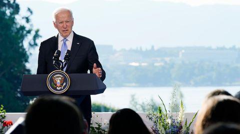 Mit dem Genfer See im Rücken spricht ein weißhaariger, weißer Mann im Anzug an einem Rednerpult mit Siegel des US-Präsidenten