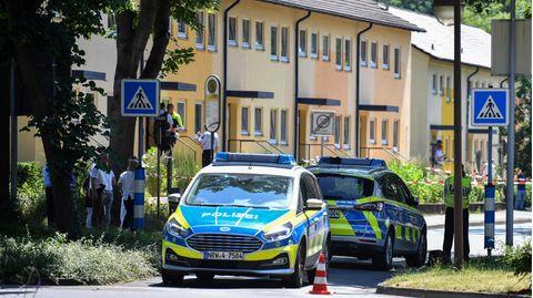 Polizeibeamte stehen vor einem Haus