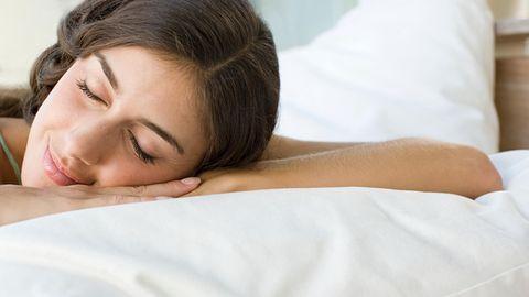 Eine junge weiße Frau mit langen, braunen Haaren liegt mit geschlossenen Augen und leicht lächelnd in einem weiß bezogenen Bett