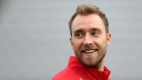 Ein weißer junger Mann in roter Jacke mit dunkelblondem Haar und Vollbart dreht lächelnd seinen Kopf über die rechte Schultert