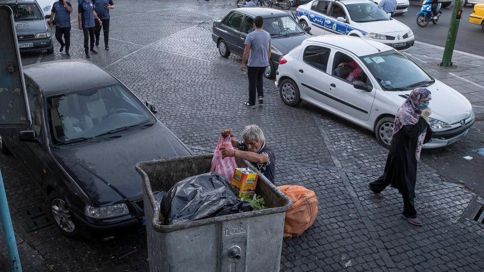 Teheran, Iran: Ein Mann durchsucht einen Müllcontainer nach Brauchbarem