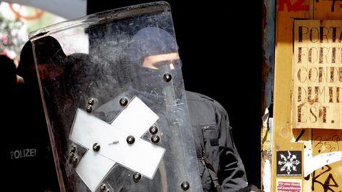 Ein Polizist mit Sturmhaube verlässt hinter einem Schild und mit Helm in der linken Hand ein heruntergekommenes Haus