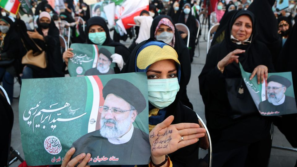 Eine Frau hält ein Plakat auf einer Wahldemo für den Präsidentschaftskandidaten Ebrahim Raisi