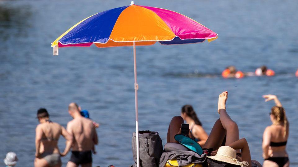 An einem Strand steht ein bunter Sonnenschirm. Erwachsene stehen in Badekleidung im Sand und schauen aufs Wasser