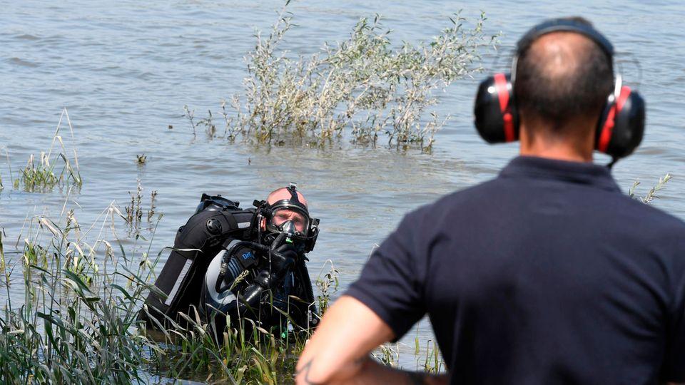 Feuerwehr-Taucher im Rhein bei Duisburg beraten sich