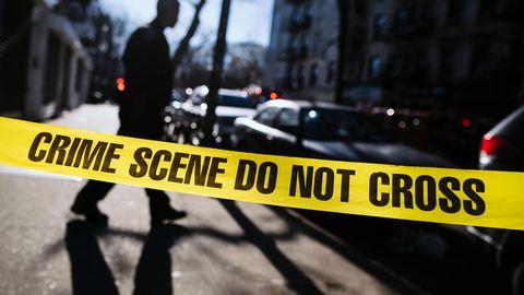 """Ein Polizist steht hinter einer gelben Absperrung mit der Aufschrift """"Crime Scene Do Not Cross"""" auf einem Fußweg"""