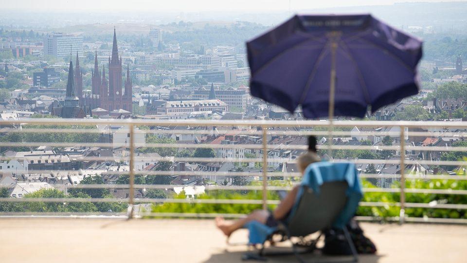 Eine Frau sitzt im Opelbad vor der Kulisse der Wiesbadener Innenstadt