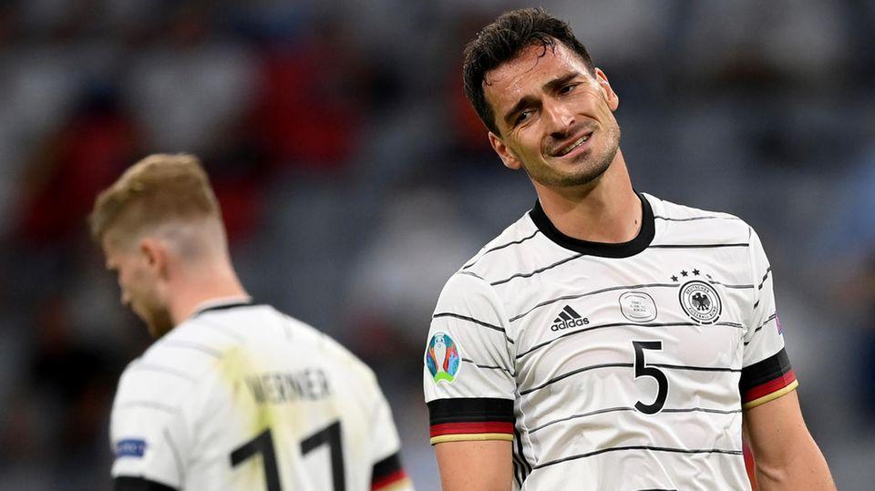 Ein weißer Mann mit kurzen, dunkelbraunen Locken steht im weißen DFB-Trikot im Stadion und lchelt gequält