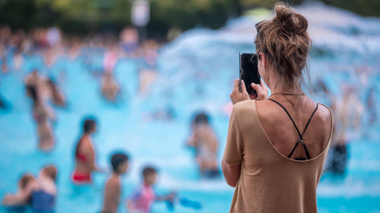 Eine junge Frau fotografiert mit ihrem Handy im Freibad