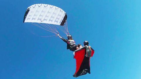 Fallschirmspringer gleitet wie auf einem Surfbrett auf der Brust einer Wingsuit-Pilotin
