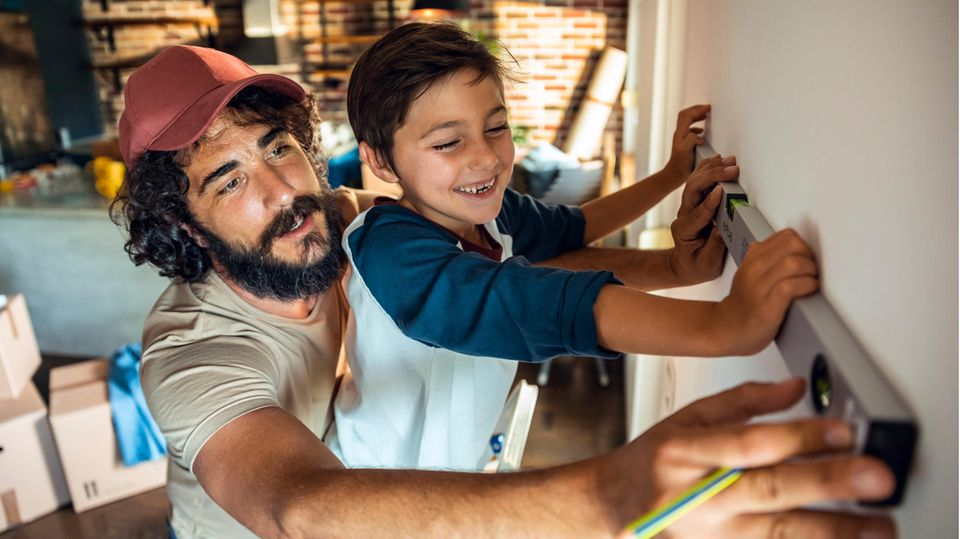 Vater und Sohn halten eine Wasserwaage an eine Wand
