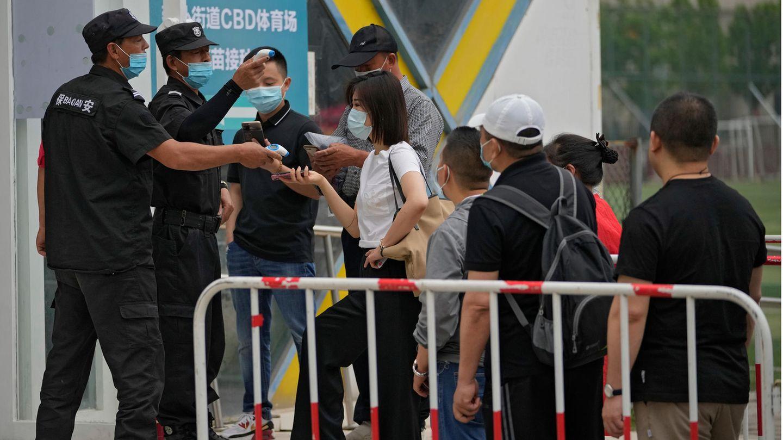 Sicherheitskräfte helfen Menschen beim Scannen ihres Gesundheitscodes