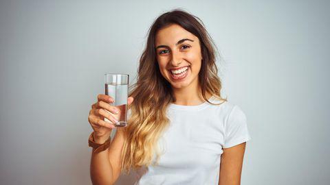 Wasser trinken Hitze: Eine Frau trinkt ein Glas mit Wasser