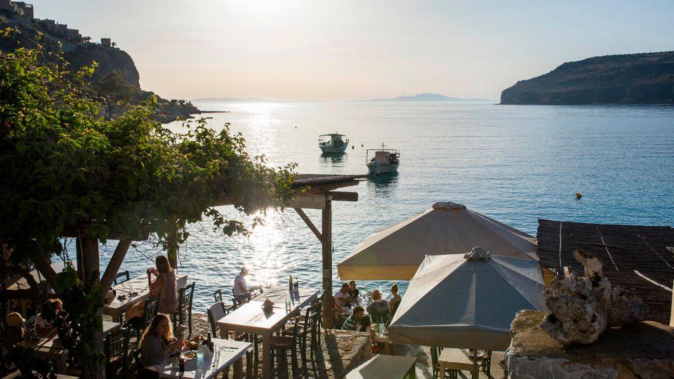 Griechenland, Limeni: Touristen sitzen in einem Café am Meer