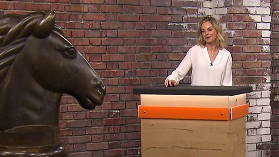 Susanne Steiger steht im Händlerraum von Bares für Rares in Pulheim neben der Bronzestatue eines Pferdekopfes
