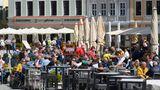 """Wer hier genau hingeguckt hat, wird recht schnell den Hinweis auf Dresden auf dem kleinen, roten Schild entdeckt haben. An der Hausfassade im Hintergrund ist zudem der Schriftzug derGrill&Bar-Lokalität """"Zum Schwan"""" zu erkennen. Kein Zweifel also, dass die Menschen hier auf dem Neumarkt an der berühmten Frauenkirche sitzen. Der ungefähre Ort bei Google Maps (hier noch mit einem anderen Lokal, da aus 2019)."""