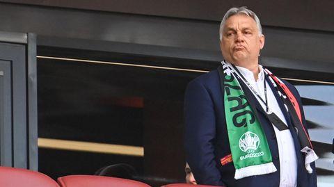 Viktor Orban schaut zufrieden. Ungarns Ministerpräsident steht mit einem um seine Schultern gelegten Fanschal an einem warmen Juni-Abend auf der Tribüne der Puskas Arena in Budapest.