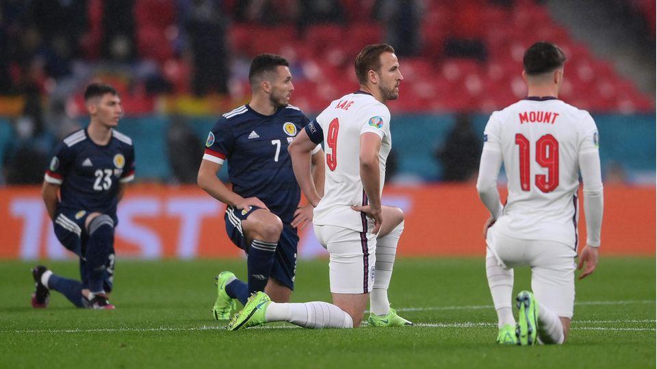 Schottische und englische Spieler knien auf dem Rasen von Wembley