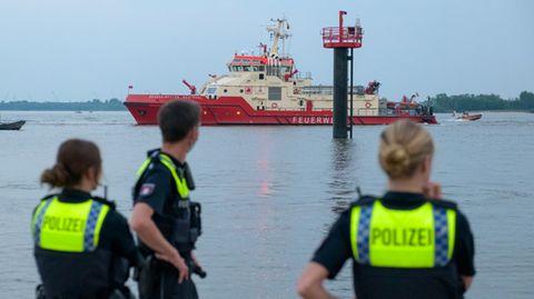 Polizisten beobachten Suchaktion auf der Elbe