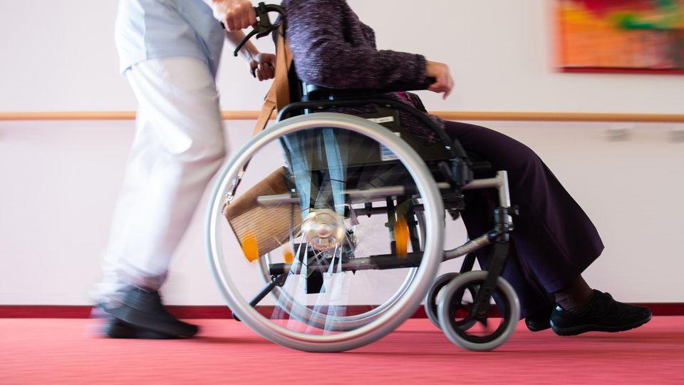 Altenpflege: Ein Pfleger schiebt eine Pflegeheimbewohnerin in einem Rollstuhl