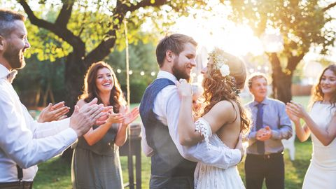 Ein Hochzeitspaar tanzt umgeben von Gästen