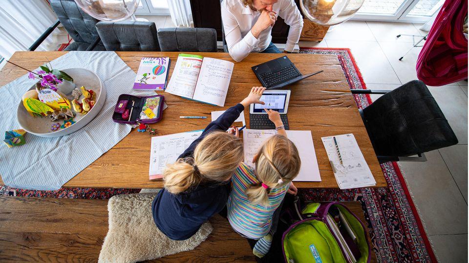 Zwei Schwestern machen im April 2021 ihre Schulaufgaben am Wohnzimmertisch.