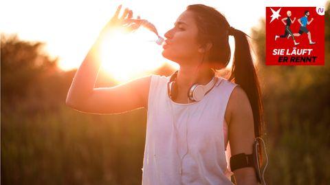 Eine Läuferin trinkt aus ihrer Wasserflasche