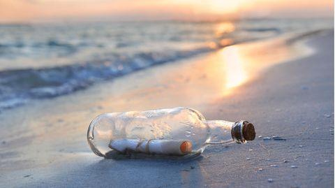 Flaschenpost liegt am Strand